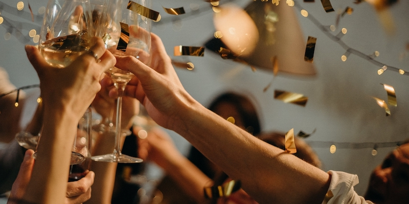 people celebrating holding up champagne glasses